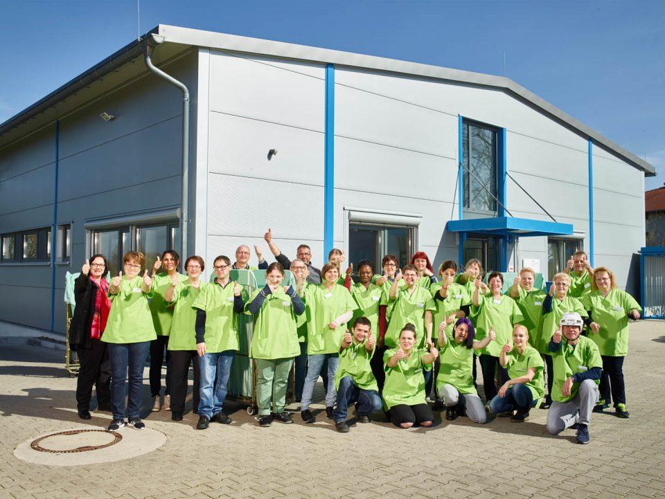 Die Mitarbeitende der Textil-Service Kork gGmbH vor dem Betriebsgebäude