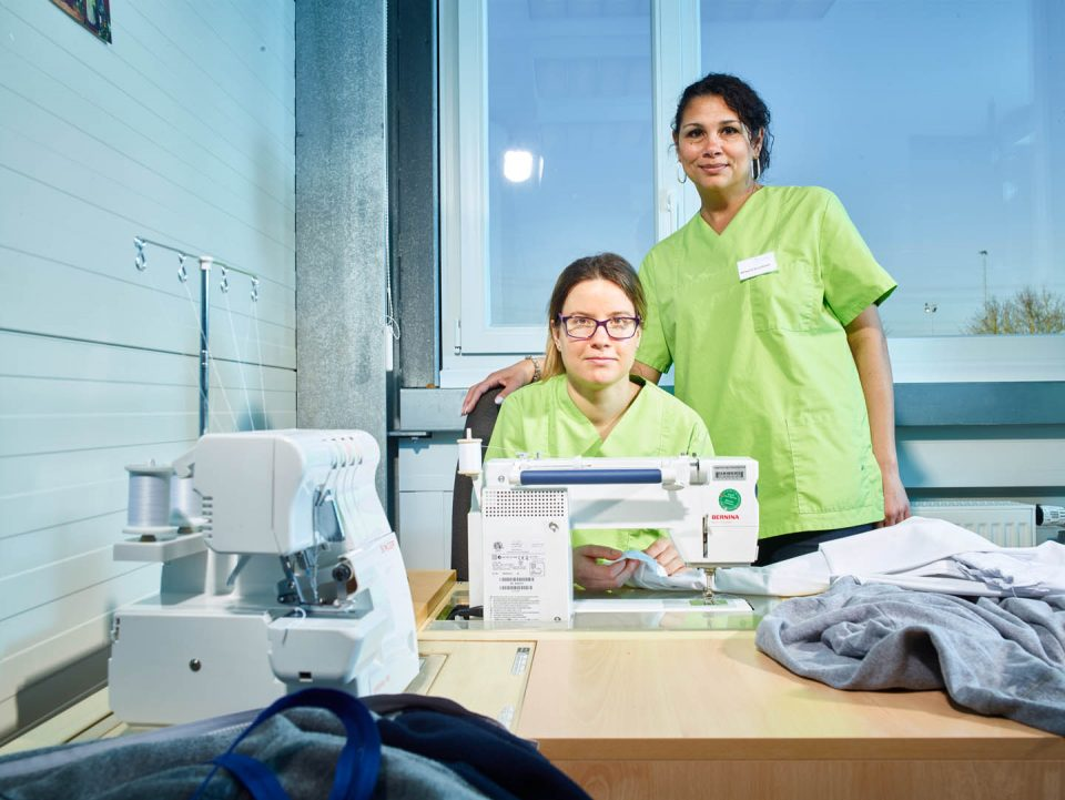 Zwei Mitarbeiterinnen der TSK, im Vordergrund zwei Nähmaschinen