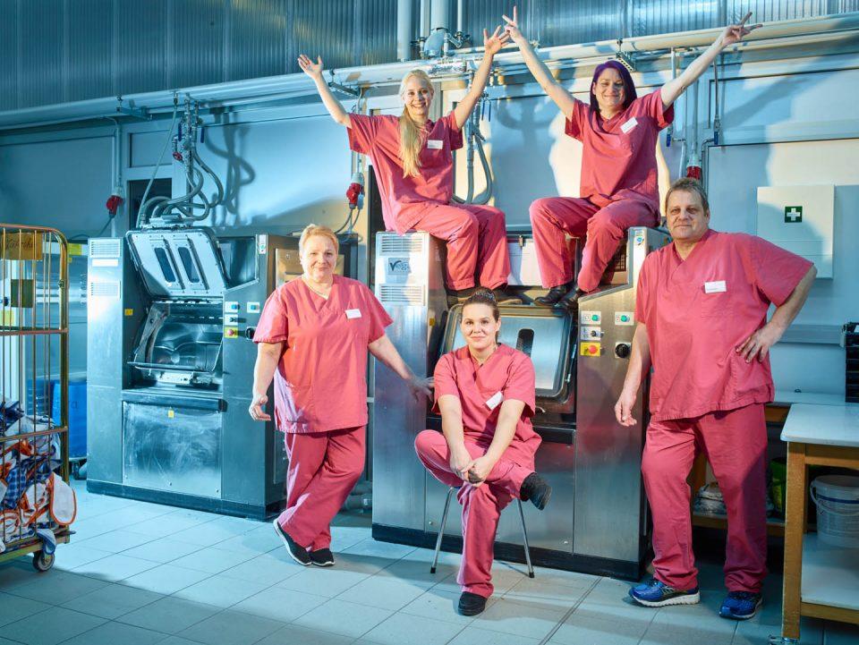 Fünf Mitarbeiter(innen) vor den großen Waschmaschinen